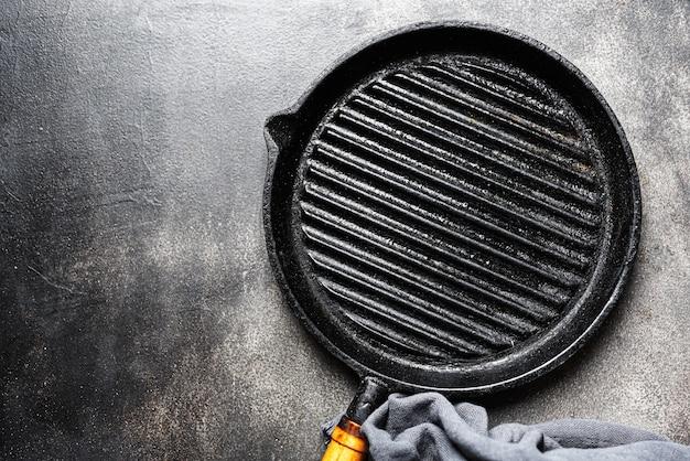 Opróżnia żelazną grill patelnię na stole
