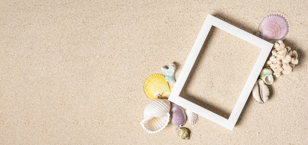 Opróżnij białą ramkę na zdjęcia i wymieszaj muszle z koralami na czystym białym piasku, widok z góry, kopia przestrzeń