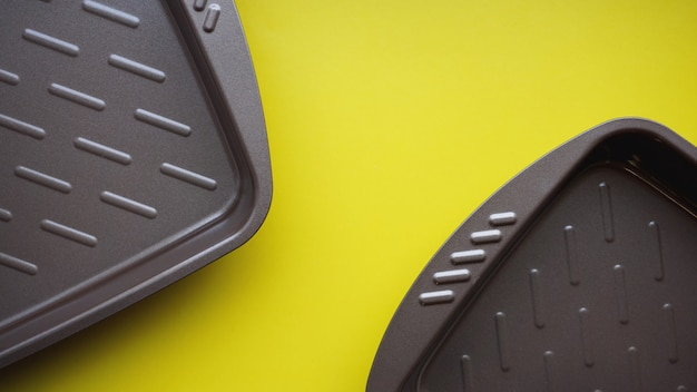 Opróżnij blachę do pieczenia. widok z góry na żółtym tle. skopiuj fotografię kosmiczną.