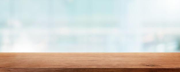 Opróżnij drewniany blat i rozmycie szklanego okna ściany budynku
