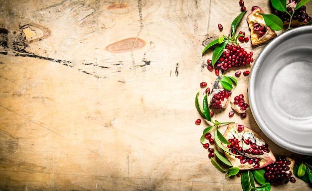 Opróżnij miskę z pestek granatu i liści wokół. na drewnianym stole. wolne miejsce na tekst. widok z góry