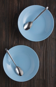 Opróżnij niebieskie naczynia z łyżkami na drewnianym stole