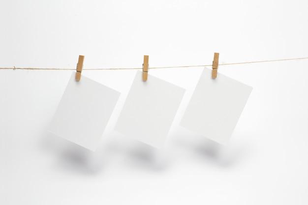 Opróżnij papierowe ramki, które wiszą na linie z spinaczami do bielizny i na białym tle. puste karty na linie.