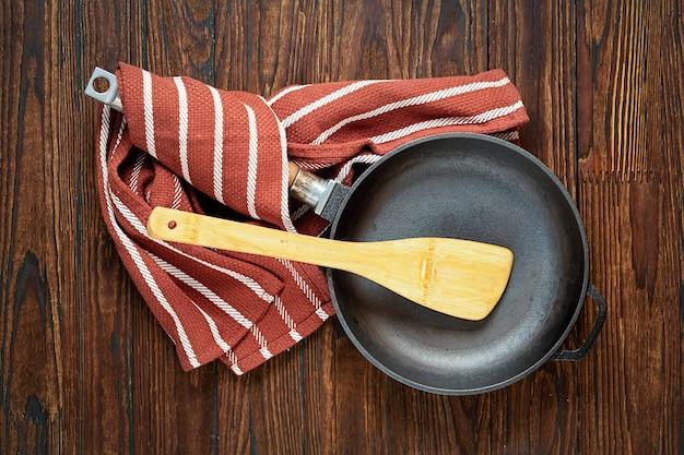 Opróżnij patelnię na drewnianym stole. koncepcja: gotowanie, kuchnia, widok z góry