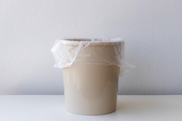 Opróżnij pojemnik na śmieci lub kosz z białą plastikową torbą
