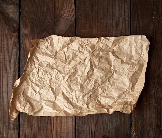 Opróżnij rozdarty kawałek brązowego zmiętego papieru do pieczenia na stole z desek