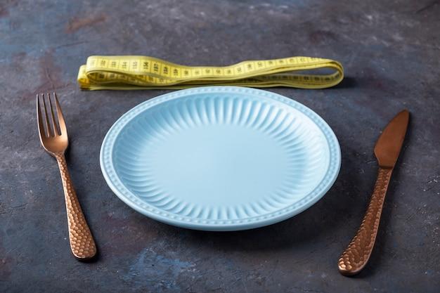 Opróżnij talerz widelcem i nożem w pobliżu taśmy pomiarowej. koncepcja odchudzania.