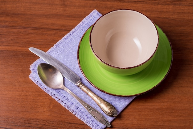 Opróżnij zielony kubek, łyżka i nóż na serwetce