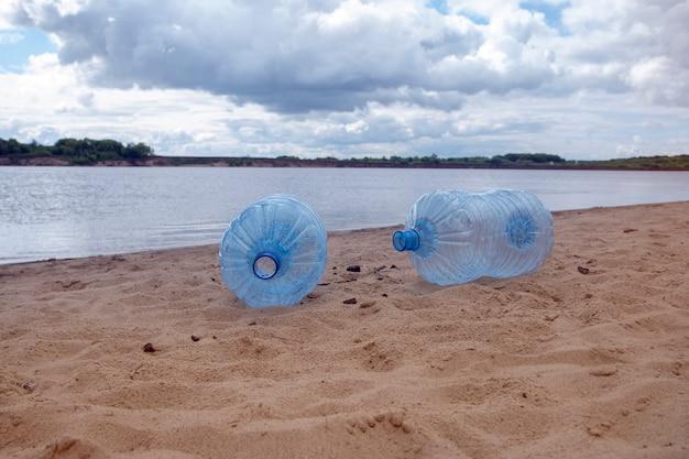 Opróżnij zużyte brudne plastikowe butelki. piaszczysty brzeg rzeki. zanieczyszczenie środowiska. problem ekologiczny.