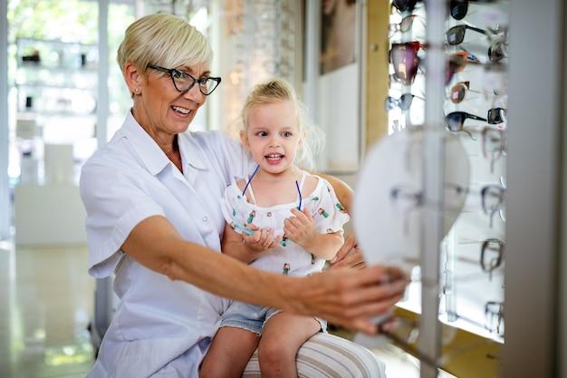 Optyk dojrzała kobieta i mała dziewczynka wybierające okulary w sklepie optycznym
