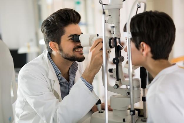 Optyk sprawdzający wzrok pacjenta i proponujący zabiegi korekcji wzroku