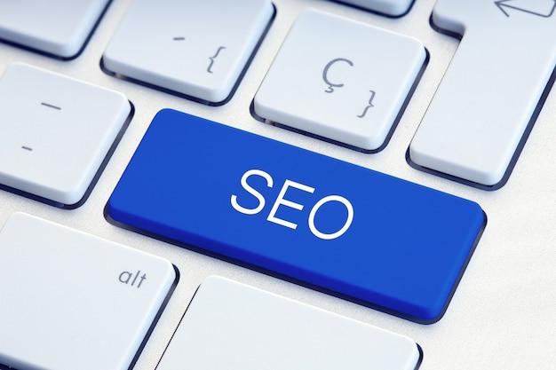 Optymalizacja dla wyszukiwarek lub słowo seo na niebieskim klawiszu klawiatury komputera
