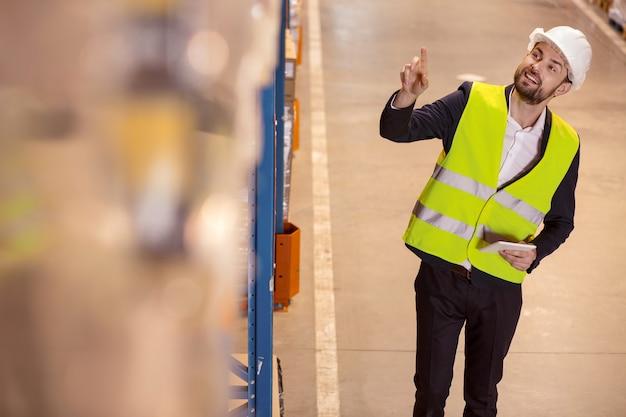 Optymalizacja przestrzeni. kierownik logistyki pozytywny uśmiechnięty, wskazując na pudełko na półce magazynowej