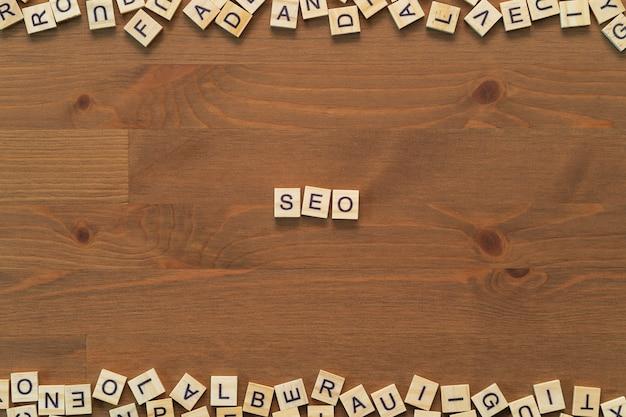 """Optymalizacja wyszukiwarki. tekst słowa """"seo"""" napisany drewnianymi literami na drewnianym biurku"""