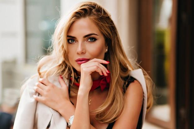 Optymistyczna blondynka o pięknych niebieskich oczach pozuje podczas odpoczynku w kawiarni w weekend