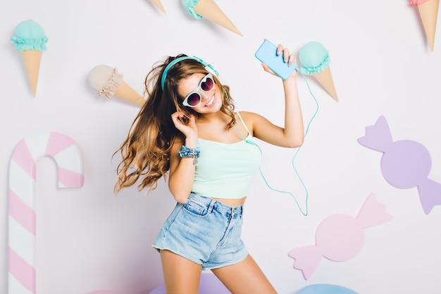 Optymistyczna dziewczyna ubrana w podkoszulek i modne dodatki tańczy z uśmiechem przy muzyce. portret radosnej młodej kobiety w okularach i słuchawkach zabawy na ścianie ozdobionej cukierkami.