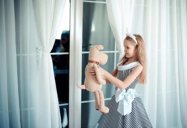 Optymistyczna dziewczyna z miękką zabawką w dłoniach, stoi przy oknie w pokoju ozdobionym na urodziny.
