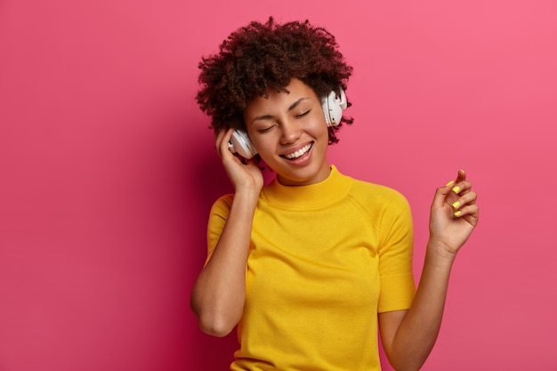 Optymistyczna etniczna dziewczyna porusza się beztrosko i słucha muzyki w słuchawkach, czuje się zrelaksowana, lubi ulubioną melodię lub nowy utwór w aplikacji z piosenkami, nosi żółte ubrania, odizolowane na różowej ścianie. technologia, gadżety