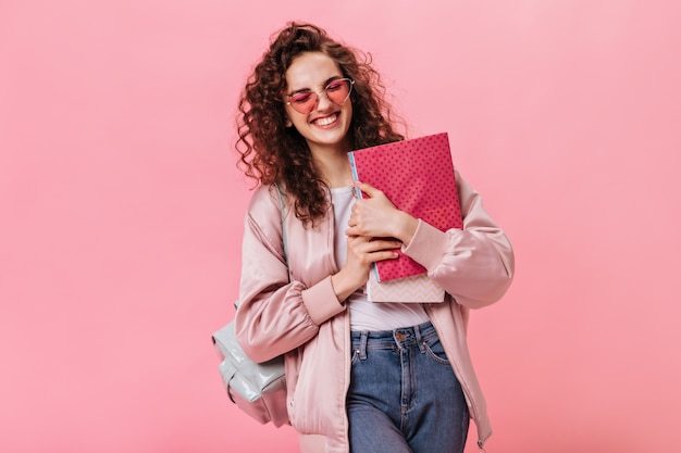 Optymistyczna kobieta trzyma zeszyty w jedwabnej kurtce i cajgach