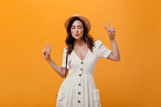 Optymistyczna kobieta w sukience i kapeluszu pokazuje oznaki pokoju na pomarańczowym tle