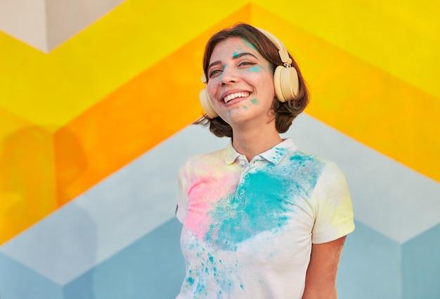 Optymistyczna młoda kobieta pokryta farbą, słuchanie muzyki