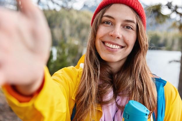 Optymistyczna modelka ma zębaty uśmiech, wyciąga rękę i robi selfie, ubrana niedbale