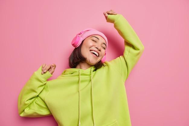 Optymistyczna nastolatka relaksuje się w pomieszczeniu, słuchając muzyki, cieszy się dobrym dźwiękiem w nowych słuchawkach, tańczy, łapie każdy kawałek, cieszy się wolnym czasem, nosi kapelusz, zieloną bluzę z kapturem, odizolowaną na różowej ścianie studia