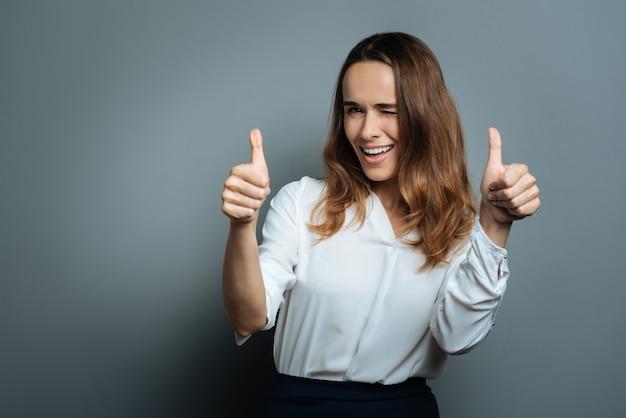 Optymistyczna osoba. szczęśliwa pozytywna zachwycona kobieta mrugająca i pokazująca kciuki do góry gestami, pokazująca jednocześnie swój optymizm