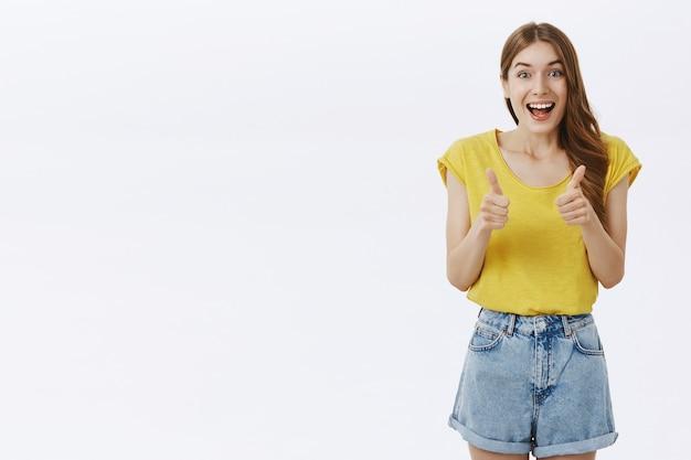 Optymistyczna piękna dziewczyna z aprobatą pokazuje kciuki do góry, lubi pomysł, zgadza się lub poleca coś niesamowitego