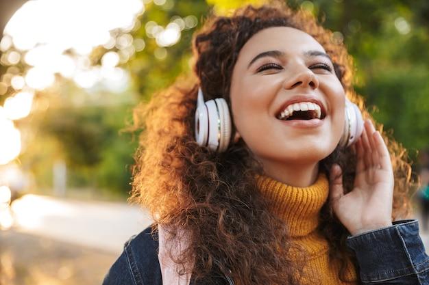 Optymistyczna piękna młoda kobieta kręcone spaceru w parku na zewnątrz słuchania muzyki w słuchawkach.