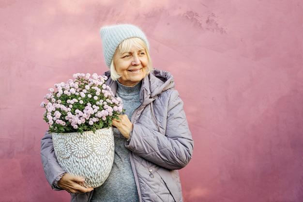 Optymistyczna starsza kobieta w ciepłych ubraniach i kapeluszu niosąca garnek z kwitnącymi kwiatami w pobliżu różowej ściany