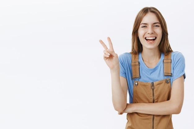 Optymistyczna szczęśliwa atrakcyjna dziewczyna pokazuje gest pokoju i śmieje się