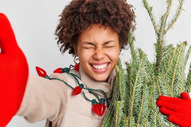 Optymistyczna, szczęśliwa, ciemnoskóra młoda kobieta robi selfie w pozach z wiecznie zielonymi uśmiechami jodły, szeroko lubi przygotowania do świąt