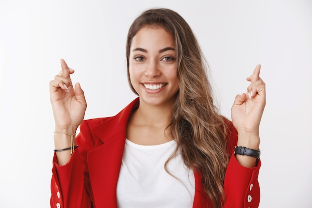 Optymistyczna szczęśliwa kobieta składająca życzenia uśmiecha się dążąc do sukcesu, krzyże trzymają kciuki, uśmiechając się, patrząc na kamerę, pełna nadziei, podekscytowana, czekająca na pozytywne wyniki, modląca się, marzące o spełnieniu się marzeń, biała ściana