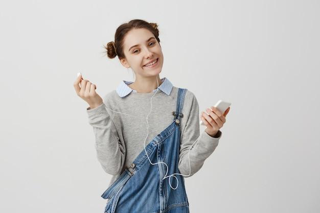 Optymistycznie dziewczyna w drelichowym gospodarstwie smartphone patrząc z miły uśmiech. kobieta dj o ładnym wyglądzie słuchająca muzyki przez słuchawki z przyjemnością. koncepcja technologii