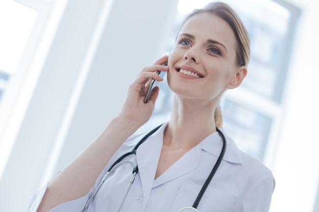 Optymistycznie pozytywnie wykwalifikowany terapeuta pracujący w szpitalu, wyrażający szczęście i cieszący się rozmową telefoniczną