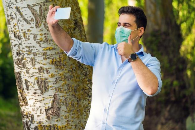 Optymistycznie przystojny mężczyzna ubrany w maskę chirurgiczną na twarzy i pokazując kciuk do góry w parku miejskim podczas rozmowy wideo