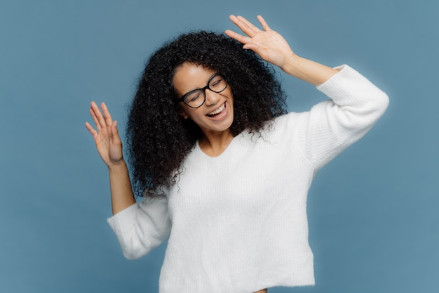 Optymistycznie zachwycona afro american kobieta podnosi ręce, tańczy do głośnej muzyki