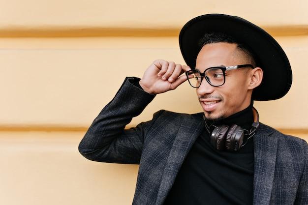 Optymistyczny afrykański mężczyzna odwracając wzrok i dotykając jego okularów. zewnątrz portret przystojny zadowolony facet w kapeluszu i kurtce w kratkę.