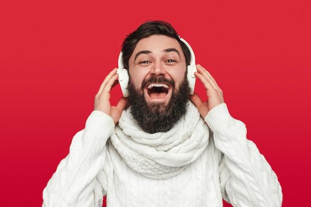 Optymistyczny brodaty mężczyzna słucha muzyki podczas obchodów bożego narodzenia