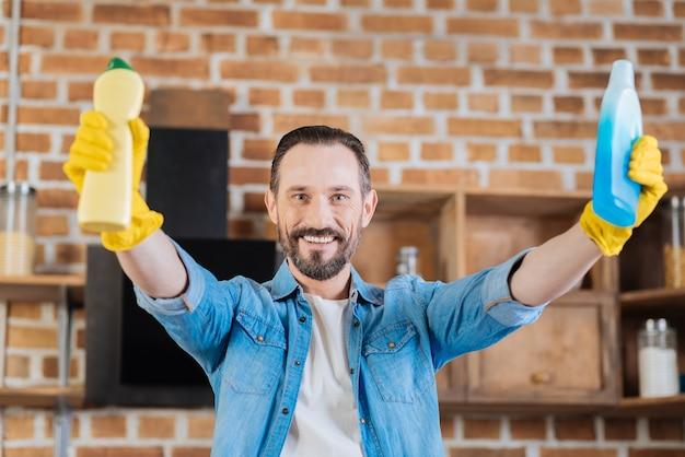 Optymistyczny brodaty mężczyzna sprzątacz rozciągający ręce środkami czyszczącymi, śmiejąc się i pozując na niewyraźnym tle