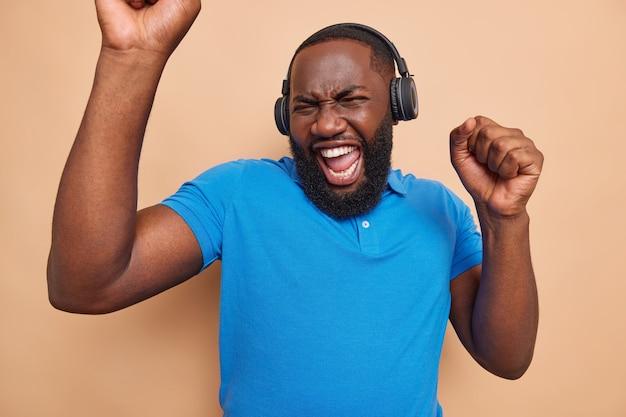 Optymistyczny ciemnoskóry mężczyzna z gęstą brodą tańczy szczęśliwie z podniesionymi rękami