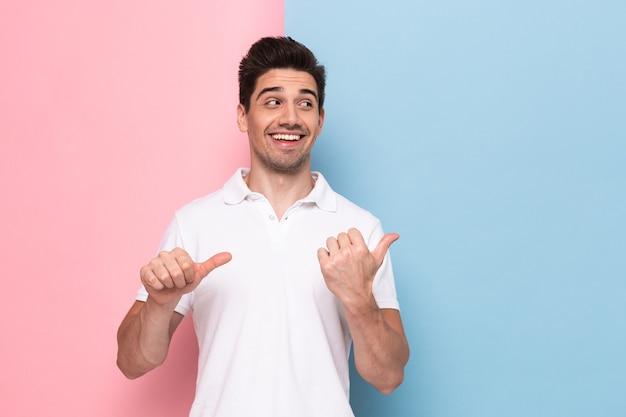 Optymistyczny człowiek o zarost wskazujący palce na copyspace, na białym tle nad kolorową ścianą