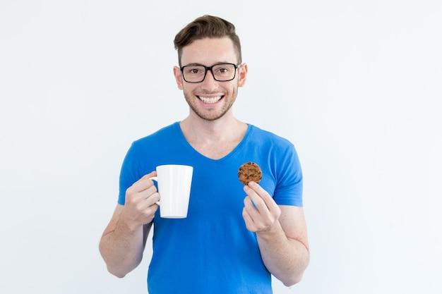 Optymistyczny facet pije kawę z ciasteczkiem