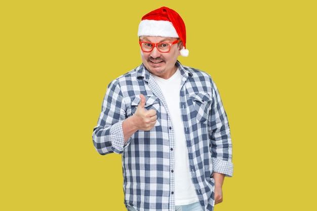 Optymistyczny mężczyzna w średnim wieku w stylu casuald w czerwonej czapce santa, stojący w okularach i pokazujący kciuki do góry i uśmiechnięty ząb, patrząc na kamerę. studio strzał, odizolowane na żółtym tle
