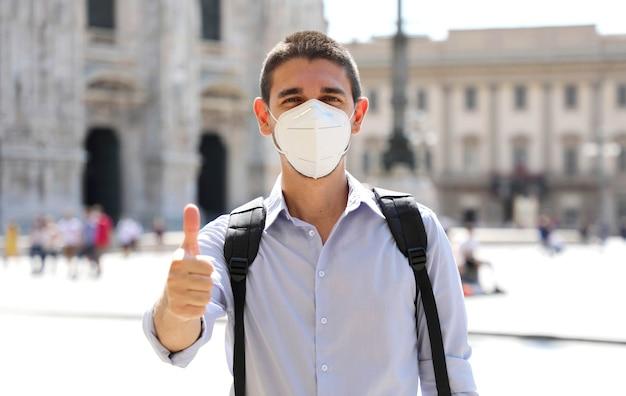 Optymistyczny młody człowiek ubrany w maskę ochronną pokazujący kciuk do góry w mediolanie we włoszech