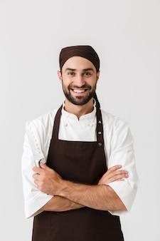 Optymistyczny młody kucharz pozuje w mundurze.