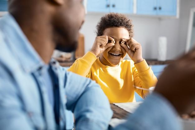 Optymistyczny nastrój. skoncentruj się na wesołym chłopcu z kręconymi włosami, wygłupiającego się podczas śniadania i uśmiechającego się radośnie, trzymając dwa pierścienie płatków obok oczu