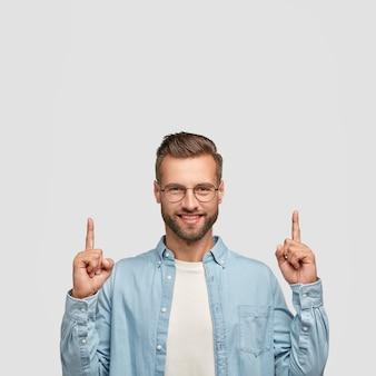 Optymistyczny, nieogolony młodzieniec ma modną fryzurę, wesoły wyraz twarzy, dwoma palcami wskazującymi wskazuje do góry, jest w dobrym nastroju