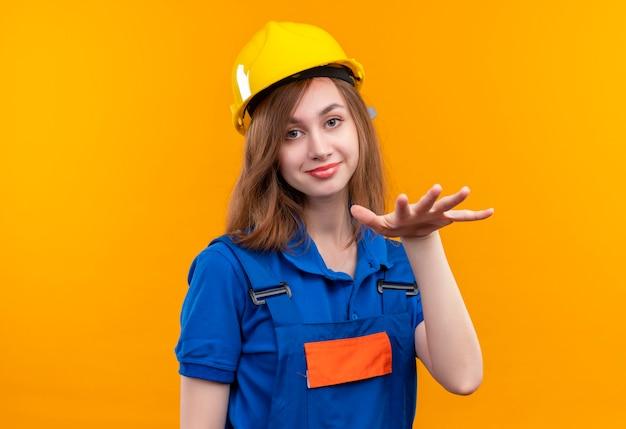 Optymistyczny pracownik budowlany młoda kobieta w mundurze budowlanym i kasku ochronnym prosząc o relaks, uspokajając gestem ręką uśmiechniętą